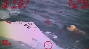 In this Sunday, Oct. 4, 2015 photo made from video and released by the U.S. Coast Guard, a Coast Guard crew member investigates a life boat, that was found from the missing ship El Faro. On Monday, four days after the ship vanished, the Coast Guard concluded it sank near the Bahamas in about 15,000 feet of water. One unidentified body in a survival suit was spotted, and the search went on for any trace of the other crew members. The search continued Tuesday, Oct. 6, 2015. (U.S. Coast Guard via AP)