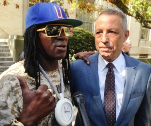 Entertainer Flavor Flav, left, standing with attorney Todd Greenberg, speaks with reporters after pleading guilty to one count of aggravated unlicensed operation of a motor vehicle, Tuesday, Oct. 13, 2015, in Mineola, N.Y. Flav, whose real name is William Drayton, Jr., was arrested in January, 2014 while racing to his mother's funeral on Long Island. A judge in Nassau Criminal Court on Tuesday sentenced Flav to time served, essentially the time he was in custody following the arrest. He was fined $3,600. (AP Photo/Frank Eltman)