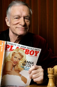 FILE - In this April 5, 2007 file photo, Playboy Enterprises founder Hugh Hefner poses with a copy of Playboy magazine featuring Anna Nicole Smith as Playmate of the Year, at the Playboy Mansion in Los Angeles. The magazine that helped usher in the sexual revolution in the 1950s and '60s by bringing nudity into America's living rooms announced this week that it will no longer run photos of completely naked women. Starting in March, 2016, Playboy's print edition will still feature women in provocative poses, but they will no longer be fully nude. (AP Photo/Damian Dovarganes, File)