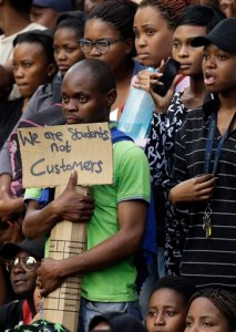 A student holds a placard during their protest against university tuition hikes outside the ruling party, African National Congress (ANC), headquarters in Johannesburg, South Africa, Thursday, Oct. 22, 2015. South African police say 30 students were arrested during a protest against university tuition hikes outside parliament in Cape Town on Wednesday. The protest turned violent when students forced their way through a parliament gate and approached the building. (AP Photo/Themba Hadebe)