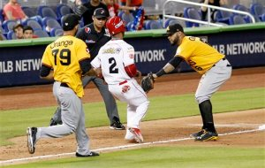 Cardenales' Elvis Escobar (2) is caught in a rundown by Aguilas third baseman Jonathan Villar as Richard Rodriguez (79) trails during the fifth inning during the championship baseball game pf Serie de las Americas at Marlins Park in Miami, Sunday, Nov. 22, 2015. (AP Photo/Joe Skipper)