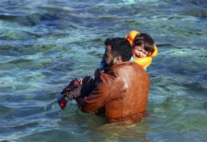 A man carries a child to a dinghy as migrants prepare to travel by dinghy from the Turkish coast to the Greek island of Chios, near Cesme, Turkey, Monday, Nov. 9, 2015. Well over half a million migrants have arrived in Greece from Turkey and the vast majority don't want to stay so head north through the Balkans to other, more prosperous European Union countries.(AP Photo/Emre Tazegul)