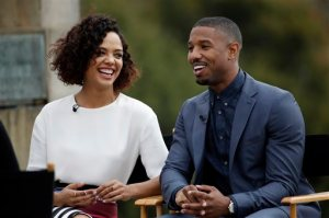 "FILE - In this Friday, Nov. 6, 2015 file photo, Michael B. Jordan, right, and Tessa Thompson laugh during an interview while promoting their film ""Creed"" outside the Philadelphia Museum of Art, in Philadelphia. While characters wearing eyeglasses - real or as props - are commonplace in movies and TV, hearing aids are seldom seen on the screen - especially on leading ladies. That's why actress Thompson was so honored to portray a strong woman character who wears the devices in the upcoming Rocky franchise spinoff, ""Creed,"" in theaters Nov. 27. (AP Photo/Matt Slocum, File)"