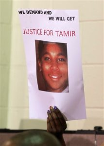 FILE- This Dec. 8, 2014 file photo shows a person holding up a sign for justice for Tamir Rice during a news conference in Cleveland. A white Cleveland police officer had no choice but to fatally shoot a 12-year-old black boy carrying a pellet gun, an expert on police use of force said in a report released publicly Thursday, Nov. 12, 2015, by the Cuyahoga County Prosecutor's Office. Retired Florida police officer W. Ken Katsaris is the third expert who has concluded that patrolman Timothy Loehmann was justified in shooting Tamir Rice outside a Cleveland recreation center Nov. 22, 2014.  (AP Photo/Tony Dejak, File)