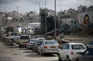 In this Tuesday, Nov. 10, 2015 photo, Palestinians wait in traffic to enter Jerusalem at Qalandia checkpoint between Jerusalem and the West Bank city of Ramallah. A pair of new mobile apps hopes to help Palestinians navigate their way around snarled traffic at Israeli checkpoints in the West Bank, offering a high-tech response to an intractable problem: constant, burdensome and often seemingly random restrictions on movement.  (AP Photo/Majdi Mohammed)