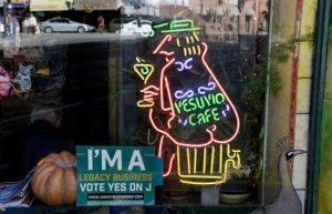 In this photo taken Thursday, Oct. 29, 2015, an election sign supporting the historic preservation of legacy business is seen in the window of the Vesuvio Cafe in San Francisco. San Francisco voters will decide Tuesday whether to restrict Airbnb operations in the city, impose a freeze on luxury housing in the Mission and approve a $310 million bond for affordable housing. They will also vote on whether to retain Mayor Ed Lee, probably yes as he faces no real competition, but could boot out the sheriff. The saloon dates to 1948 and was a regular hangout to Jack Kerouac and other Beat poets. (AP Photo/Eric Risberg)