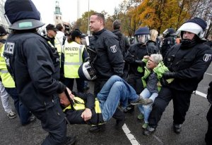 "Police officers carry away people who tried  to stop a protest rally of the German party 'Alternative fuer Deutschland, AfD' (Alternative for Germany) in Berlin, Germany, Saturday, Nov. 7, 2015. The  anti-immigration party AfD  has staged a march in Berlin against the German government's migrant policies, with demonstrators chanting ""Merkel must go"" and counter-protesters shouting ""Nazis out.""  (AP Photo/Michael Sohn)"