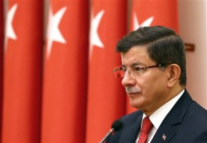 """Turkish Prime Minister Ahmet Davutoglu attends an annual meeting of High Military Council  in Ankara, Turkey, Thursday, Nov. 26, 2015. Davutoglu is seeking to reduce tensions with Moscow, saying that Russia is Turkey's """"friend and neighbor"""" and insisting relations cannot be """"sacrificed to accidents of communication."""" Davutoglu said on Wednesday that Turkey didn't know the nationality of the plane that was brought down at the border with Syria on Tuesday until Moscow announced it was Russian.(AP Photo/Prime Minister's Press Service, Pool)"""