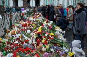 People gathered to lay flowers in memory of the plane crash victims at Dvortsovaya (Palace) Square in St.Petersburg, Russia, on Wednesday, Nov. 4, 2015. A Russian official says families have identified the bodies of 33 victims killed in Saturday's plane crash over Egypt. The Russian jet crashed over the Sinai Peninsula early Saturday, killing all 224 people on board, most of them were holidaymakers. (AP Photo/Ivan Sekretarev)
