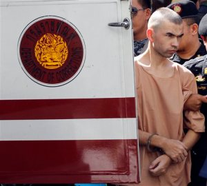 Police officers escort a suspect in the Aug. 17 blast at Erawan Shrine, Bilal Mohammad, right, on his arrival at a military court in Bangkok, Thailand, Tuesday, Nov. 24, 2015. The military court has indicted two men police say carried out the deadly August bombing at the shrine that left 20 people dead and more than 120 injured. (AP Photo/Sakchai Lalit)