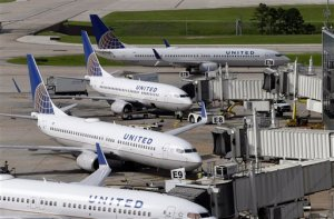 FILE - In this July 8, 2015 file photo, United Airlines planes are parked at their gates as another plane, top, taxis past them at George Bush Intercontinental Airport in Houston. U.S. airlines have ramped up an aggressive lobbying campaign that seeks nothing less than converting the government from industry regulator to business ally. The big three legacy carriers, Delta, American and United, want the Obama administration to protect them from competition from foreign airlines, arguing those rivals can undercut ticket prices thanks to government subsidies or cheaper labor.  (AP Photo/David J. Phillip, File)