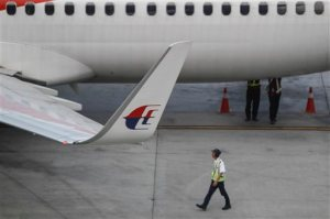 A Malaysia Airlines ground staff walks past a taxied aircraft on the tarmac of Kuala Lumpur International Airport in Sepang, Malaysia, Tuesday, Oct. 13, 2015. A Russian state-controlled missile-maker said Tuesday its investigation of last year's crash of a Malaysia Airlines plane over rebel eastern Ukraine contradicts conclusions from a Dutch probe. (AP Photo/Joshua Paul)