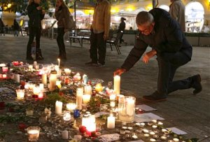 A man pays tribute to the victims of the terror attacks in Paris in Nice, southeastern France, Monday, Nov. 16, 2015. France is urging its European partners to move swiftly to boost intelligence sharing, fight arms trafficking and terror financing, and strengthen border security in the wake of the Paris attacks. (AP Photo/Lionel Cironneau)