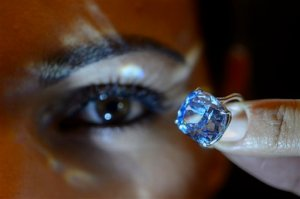 FILE - In this Nov. 4, 2015 file photo a Sotheby's employee displays the rare Blue Moon Diamond during a preview at  Sotheby's, in Geneva, Switzerland. The 12.03 carat blue diamond is the largest cushion shaped fancy vivid blue diamond  ever appear at auction. It is estimated to sell between 35 and 55 million US dollars. The auction will take place in Geneva, on Nov. 11, 2015. (Martial Trezzini/Keystone via AP, file)