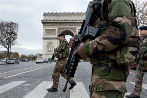French soldiers cross the Champs Elysees avenue passing the Arc de Triomphe in Paris, Monday, Nov. 16, 2015. While few in the war-weary West want to send ground troops to the areas controlled by Islamic State, it may actually be even harder to find anyone arguing that the aerial bombardment strategy will soon succeed in defeating the radical jihadi group. That is the fundamental contradiction faced by policymakers as they grapple with the meaning of the Paris attacks. (AP Photo/Peter Dejong)