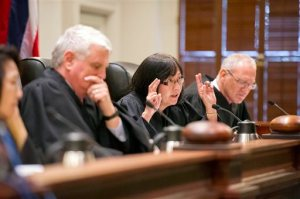 FILE- In this Aug. 27, 2015, file photo, Chief Justice Mark Recktenwald, from left, Associate Justice Sabrina S. McKenna, and Associate Justice Michael Wilsonas preside as oral arguments at the Hawaii State Supreme Court. The case involves building one of the world's largest telescopes on Mauna Kea. The Hawaii Supreme Court said Tuesday, Nov. 17, that it is temporarily suspending a permit that allows the giant telescope to be built on a mountain many Native Hawaiians consider sacred. (Craig T. Kojima/Honolulu Star-Advertiser via AP, Pool, File)
