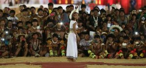 """In this Oct. 24, 2015 photo, indigenous men take photos of a Pataxo indigenous woman from Brazil during a """"parade of indigenous beauty"""" at the World Indigenous Games in Palmas, Brazil. The Indigenous Games' organizers stressed it wasn't a beauty contest _ no queen was crowned, no runners-up selected.  It was, they insisted, a celebration of facial features, body types and adornments not often given their due. (AP Photo/Eraldo Peres)"""