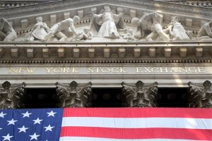 In this July 6, 2015, file photo, an American flag is draped on the exterior of the New York Stock Exchange. International stock markets fell Monday, Nov. 16, 2015, after the attacks in Paris last week sent worries across the world about their possible economic effects. Futures point to Wall Street drifting lower on Monday. (AP Photo/Mark Lennihan, File)
