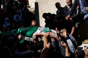 A Palestinian boy looks as mourners carry the body of  27-year-old Abdallah Shalaldeh, during his funeral in the West Bank village of Sa'ir, near Hebron, Thursday, Nov. 12, 2015. Israeli forces disguised in traditional Arab outfits, including one impersonating a pregnant woman and others appearing to have fake facial hair, burst into a hospital overnight Thursday, killing Shalaldeh during an arrest raid caught on video. (AP Photo/ Nasser Shiyoukhi)