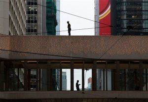 A worker stands on top of a bridge between commercial buildings in Central, the financial district of Hong Kong, Tuesday, Nov. 10, 2015. Asian stock markets extended losses Tuesday as investors fretted over the fragile outlook for global growth and the Federal Reserve's plan to raise U.S. interest rates soon. (AP Photo/Kin Cheung)