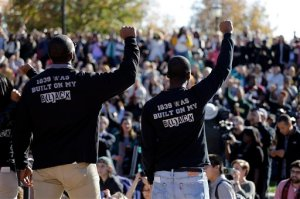 In this photo taken Nov. 9, 2015, members of the black student protest group, Concerned Student 1950, raise their arms while addressing a crowd following the announcement University of Missouri System President Tim Wolfe would resign, at the University of Missouri in Columbia, Mo. On the campaign trail, among candidates of both parties, the idea of locking up drug criminals for life is a lot less popular than it was a generation ago. The 2016 presidential race has accelerated an evolution away from the traditional tough-on-crime candidate. A Republican Party that's long taken a law-and-order stance finds itself desperate to improve its standing among minority voters while Democratic candidates are also being drawn into national conversations on policing, drug crimes and prison costs. (AP Photo/Jeff Roberson)