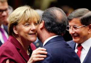 German Chancellor Angela Merkel welcomes French President Francois Hollande while Turkish Prime Minister Ahmet Davutoglu, right, looks on during an EU-Turkey summit at the EU Council building in Brussels on Sunday, Nov. 29, 2015. At a high-profile summit in Brussels on Sunday, European Union leaders will look to offer Turkey 3 billion euros ($3.2 billion), an easing of visa restrictions and the fast-tracking of its EU membership process in return for tightening border security and take back some migrants who don't qualify for asylum.(AP Photo/Michael Probst)