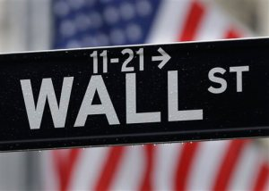 FILE - This July 9, 2015, file photo, shows a Wall Street sign near the New York Stock Exchange. Global stock markets drifted lower Thursday, Nov. 12, 2015, as investors looked past some fairly dovish remarks from the head of the European Central Bank and awaited a slew of comments from Federal Reserve officials, notably those of Fed Chair Janet Yellen. (AP Photo/Seth Wenig, File)