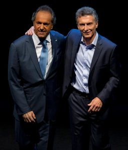 In this Nov. 15, 2015 photo, opposition presidential candidate Mauricio Macri, right, and Daniel Scioli, the ruling party presidential candidate embrace each other on stage at the end of the presidential debate in Buenos Aires, Argentina. Macri will face Scioli in a Nov. 22 runoff. Macri promises to maintain a safety net for the poor but says he will overhaul the economy to address inflation estimated around 30 percent and a byzantine monetary system that has spawned a booming black market. (AP Photo/Natacha Pisarenko)