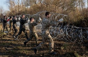 Slovenian solders erect razor wire fence in Rakovec, Slovenia, Thursday, Nov. 12, 2015. European leaders scrambled Thursday to keep their passport-free travel zone from collapsing, after Germany, Sweden and Slovenia acted on their own to tighten borders or erect fences to slow the relentless influx of people marching into Europe. (AP Photo/Darko Bandic)