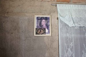 This Sept. 23, 2015 photo shows Yainis Souto's portrait when she was 15-years-old, as well as a photo of her with her then-boyfriend Jose Fuentes Lastre, inside her home in Camaguey, Cuba. Souto and Lastre broke up while they tried to maintain a long distance relationship, with Lastre in the U.S. and Souto in their childhood neighborhood of Porvenir. (AP Photo/Christine Armario)
