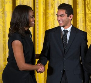 First lady Michelle Obama shakes hands with Ibrahim Shkara of The Telling Room in Portland, Maine during the 2015 National Arts and Humanities Youth Program Awards, Tuesday, Nov. 17, 2015, in the East Room of the White House in Washington. The award goes to students representing 12 after-school programs from across the country and 1 international program. (AP Photo/Evan Vucci)