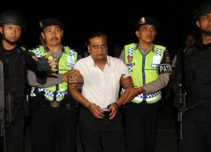 """Indian fugitive Rajendra Sadashiv Nikalje, known in India as """"Chotta Rajan,"""" center, is escorted by police officers to the Bali airport to be deported, Indonesia, Thursday, Nov. 5, 2015. The alleged organized crime boss, wanted for alleged involvement in several mafia killings and other major crimes in his homeland, was arrested Sunday after arriving at Bali's airport from Sydney based on information from Interpol and Australian authorities. (AP Photo/Firdia Lisnawati)"""