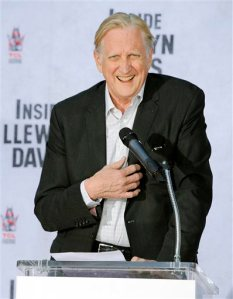 """FILE - In this Nov. 14, 2013 file photo, T-Bone Burnett, executive music producer of the film """"Inside Llewyn Davis,"""" addresses the crowd during a hand and footprint ceremony for cast member John Goodman in Los Angeles. Burnett, known for keeping alive forms of American roots music, replaces the previously announced songwriting team of Alan Menken and Glenn Slater, who were unable to continue on """"Happy Trails"""" due to a scheduling conflict. (Photo by Chris Pizzello/Invision/AP, File)"""