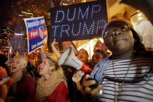 "Sasha Murphy, of the ANSWER Coalition, leads demonstrators in a chant during a protest against Republican presidential candidate Donald Trump's hosting ""Saturday Night Live"" in New York, Saturday, Nov. 7, 2015. Despite a 40-year history of lampooning politicians while inviting some to mock themselves as on-air guests, booking a presidential candidate to host the NBC sketch-comedy show is almost unprecedented. (AP Photo/Patrick Sison)"