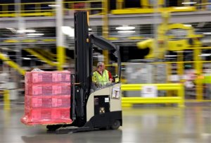 FILE - In this Feb. 13, 2015, file photo, a forklift operator moves a pallet of goods at an Amazon.com fulfillment center in DuPont, Wash. This year, Amazon has been making an aggressive push to offer same-day delivery to its $99 annual Prime loyalty club members. Their service is now available in 750 cities and towns in 16 metro areas. And where Amazon goes, other retailers must follow. (AP Photo/Ted S. Warren, File)