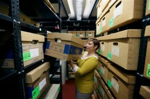 In a photo from Thursday, Oct. 22, 2015, in Ann Arbor, Mich., Olga Virakhovskaya Lead Archivist for Collections Management, Bentley Historial Museum, University of Michigan moves a box containing files on assisted suicide that belonged to Dr. Jack Kevorkian.The archive, donated by Ava Janus, Kevorkian's niece and sole heir, is stored in one of nine boxes in the stacks of the Bentley Historical Library in Ann Arbor. (AP Photo/Carlos Osorio)