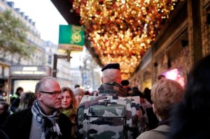A soldier patrols in front of the Galeries Lafayette department store in Paris over a week after the start of the Paris attacks, Sunday, Nov. 22, 2015. French President Francois Hollande will preside over a national ceremony on Nov. 27 honoring the victims of the deadliest attacks on France in decades. (AP Photo/Laurent Cipriani)