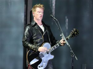 """FILE - In this Jan. 26, 2014 file photo, Joshua Homme, of Queens of the Stone Age, performs at the 56th annual Grammy Awards in Los Angeles. Homme, also a member of Eagles of Death Metal, was scheduled to perform, Friday, Nov. 13, 2015, at the Bataclan venue in Paris where patrons were taken hostage. The band says they are home safe after the Paris attacks, but they """"are horrified and still trying to come to terms with what happened in France."""" The band released a new album last month and was on an European tour when the attacks occurred. They said all shows are on hold until further notice. (Photo by Matt Sayles/Invision/AP, File)"""