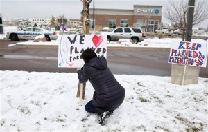 Bethany Winder, a nurse who lives in Colorado Springs, Colo., plants a sign in support of Planned Parenthood just south of its clinic as police investigators gather evidence near the scene of Friday's shooting at the clinic Sunday, Nov. 29, 2015, in northwest Colorado Springs. (AP Photo/David Zalubowski)