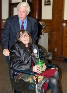Linda Horan arrives with her lawyer Paul Twomey, rear, for a hearing at Merrimack County Superior Court Thursday, Nov. 12, 2015, in Concord, N.H.  Horan, in late-stage of lung cancer, seeks a court to provide her a medical marijuana identification card before dispensaries open next year in New Hampshire. The card would permit her to obtain marijuana in Maine, which serves patients who have registry cards in their home states. (AP Photo/Lynne Tuohy)