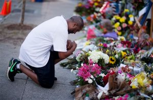 FILE - In this June 20, 2015 file photo, Harold Jackson of Tyler, Texas, kneels while visiting a sidewalk memorial in front of Emanuel AME Church in Charleston, S.C., several days after nine people were killed inside the church during a Bible study. A group of archivists said  Nov. 11, 2015 that almost five months after the tragedy, the laborious work of cataloguing and preserving mementoes left outside or given to the church continues. (AP Photo/David Goldman, file)