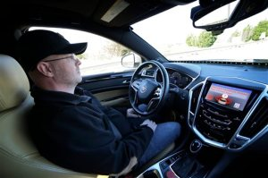This Friday, Nov. 13, 2015, photo provided by Virginia Tech shows Greg Brown, technology development program administration specialist, sitting behind the wheel of a self-driving car during a test ride on a local street in Blacksburg, Va. The vehicle's alert system is handing over control to Brown as it disengages from self-driving mode. (Justin Fine/Virginia Tech via AP)