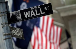 FILE - This Oct. 2, 2014 file photo shows a Wall Street sign adjacent to the New York Stock Exchange, in New York.  European shares shed earlier gains Thursday, Dec. 3, 2015 after the European Central Bank failed to cut a key interest rate as much as many in the markets had expected. (AP Photo/Richard Drew, File)