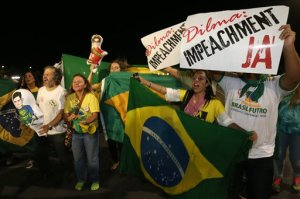 """People demonstrate against the government as they take part in protest in favor of the impeachment of Brazil's President Dilma Rousseff, in front of the National Congress, in Brasilia, Brazil, Wednesday, Dec. 2, 2015. Impeachment proceedings were opened Wednesday against Brazilian President Rousseff by the speaker of the lower house of Congress, a sworn enemy of the beleaguered leader. The signs held by the demonstrators read in Portuguese """"Dilma Impeachment Now."""" (AP Photo/Eraldo Peres)"""