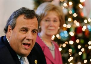 Former New Hampshire House Speaker Donna Sytek listens at right as Republican presidential candidate, New Jersey Gov. Chris Christie speaks at a drug recovery round table at Hope For Recovery, Tuesday, Dec. 1, 2015, in Manchester, N.H. Sytek endorsed Christie's presidential campaign. (AP Photo/Jim Cole)
