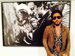 "In this image taken from video, Musician Lenny Kravitz stands in front of one of his photos from his exhibit ""Flash"", which is running in conjunction with Art Basel in Miami Beach, Wednesday, Dec. 2, 2015. Kravitz set out shooting photos on his days off while touring, hoping to capture soulful photographs and people in their environments. (AP Photo/Joshua Replogle)"