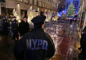 New York Police officers stand watch at an entrance to Rockefeller Center along Fifth Avenue where the Rockefeller Center Christmas tree could be seen after the lighting ceremony, Wednesday, Dec. 2, 2015, in New York. Increased security surrounded the annual event, which drew several thousand spectators. (AP Photo/Julie Jacobson)