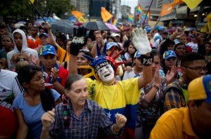 Supporters of the Mesa de la Unidad (MUD) political party  cheer during a closing campaign rally in Caracas, Venezuela, Wednesday, Dec. 2, 2015. The Dec. 6 ballot for Venezuelan congressional elections has more than two dozen parties competing in a contest that represents the stiffest challenge in 16 years for Venezuela's ruling socialist party. (AP Photo/Ariana Cubillos)