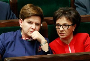 """Poland's Prime Minister Beata Szydlo,left, listens to a debate in the Parliament next to prominent member of the ruling Law and Justice party, and lawmaker Elzbieta Witek, right, in Warsaw, Poland on Wednesday, Jan. 13, 2016. Poland's prime minister says that the nation's democracy is """"doing well"""" while European Union leaders are debating the rule of law under her right-wing government. The European Council is debating opinions that democracy and media freedom in Poland are threatened by new legislation that the ruling Law and Justice party, in power since November, adopted on state broadcasters and the Constitutional Tribunal. (AP Photo/Czarek Sokolowski)"""