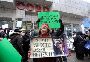 Western International High School teacher Debrah Baskin, 53, of Southfield, and other teachers from Detroit area schools protest outside the Cobo Center, Wednesday, Jan. 20, 2106, only hours before President Barack Obama's visit to the auto show. Faced with another massive sick-out by teachers, the Detroit school district filed a lawsuit Wednesday to try to stop absences that have kept thousands of students at home and left parents scrambling for child care and other quick remedies. The latest sick-out shuttered more than 85 of the struggling district's roughly 100 schools and was timed to coincide with a visit to the city by the Obama. (Todd McInturf/Detroit News via AP)  DETROIT FREE PRESS OUT; HUFFINGTON POST OUT; MANDATORY CREDIT
